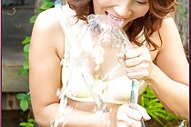 Thai girl Hiroko Rumi has fun in garden with water hose