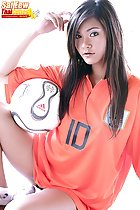 Seated with ball long hair over orange football shirt