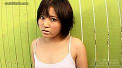 Yuki Standing Against Green Fence Wearing White Ship Short Hair