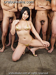 Squatting On Floor In Front Of Naked Men Wearing Bikini In Gold High Heels Hand On Knee